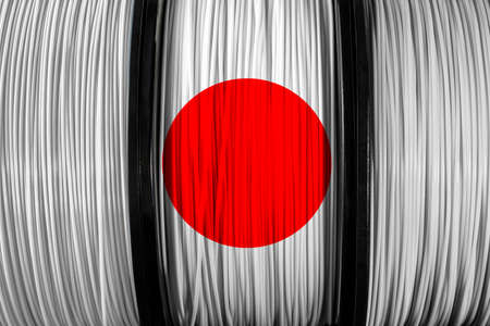 Japan flag of the coils for 3D printer. Filament for 3d printing. Bright thermoplastic of white and red colord. Reel bertical view.