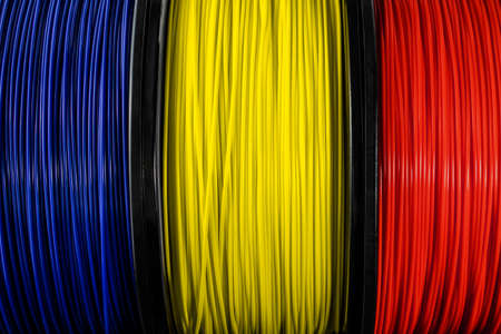 Romania flag of the coils for 3D printer. Filament for 3d printing. Bright thermoplastic of blue, yellow and red colors. Flag colors Foto de archivo
