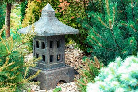 Ornamental stone lantern with among fresh green plants in a zen garden, japanese design, eastern garden design, outdoor garden stone statue decoration. Macro 免版税图像