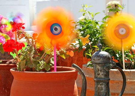 Colourful flowers, windmill and old water pot photo