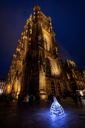 A dancer dancing in front of Strasbourg Cathedral at night Stock Photo