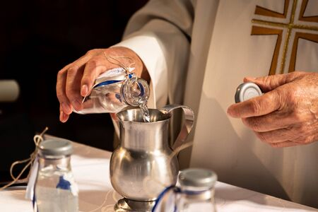 Holy water poured by a priest into a church