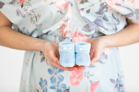 Young pregnant woman holds baby booties in front of her belly - Gender Reveal Stock fotó