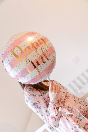 Young pregnant woman is holding pink balloons - Gender Reveal - It's a Girl !