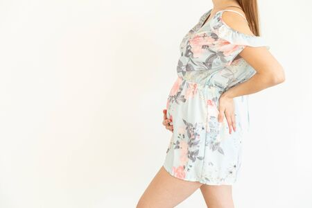 Young pregnant woman with blue dress puts her hands on her belly - Gender Reveal Reklamní fotografie