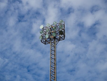 uprise: Old and tall spotlights tower with 12 bulbs at sports stadium in the morningafternoon. The background is blue sky with some clouds.