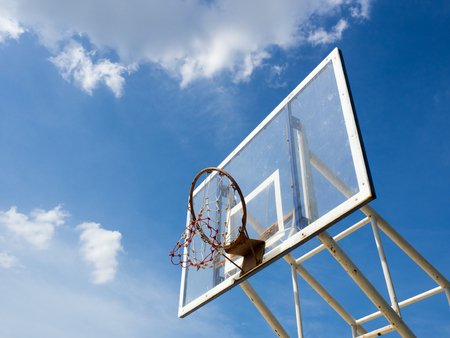 backboard: Broken old basketball hoop with backboard against  blue sky, white cloud