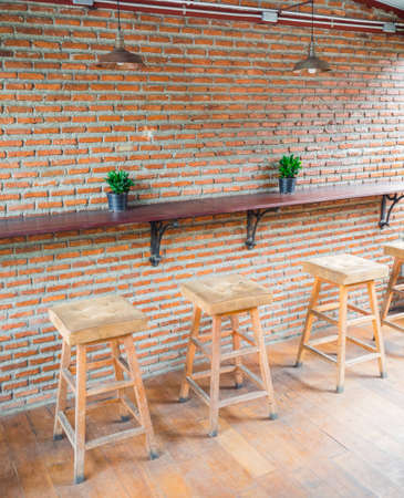 The empty cafe (Coffee shop), wooden chairs with leather seat near the bar against red/orange brick wall