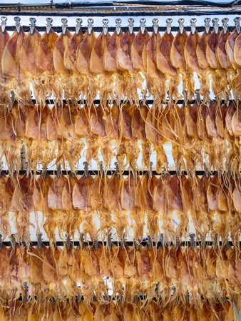 Dried squids for roastedgrilled, local food, hanging on mobile cart in a street market near the sea in Thailand. Stock Photo