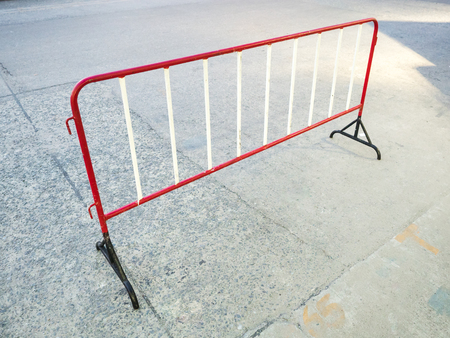 Temporary red and black steel mobile fence on concrete road