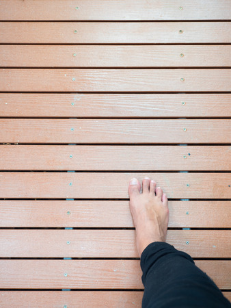 dhamma: Right mans foot walking on wooden board path Stock Photo