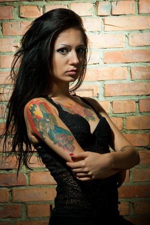 tatouage sexy: tatou� brunet sexi fille sur le fond brickwall regardant la cam�ra