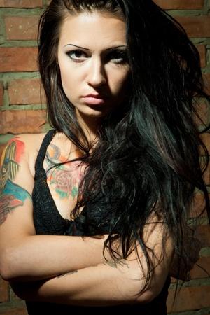 tatouage sexy: tatoués Brunet sexi fille sur le fond brickwall regardant la caméra