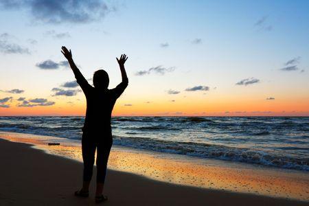Woman doing yoga at sunset photo