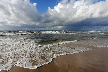 Wave crashing on a beach photo