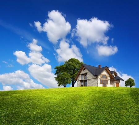 Einfamilienhaus auf einem grünen Hügel Standard-Bild