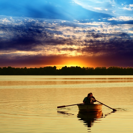 Couple in boat against a beautiful sunset photo
