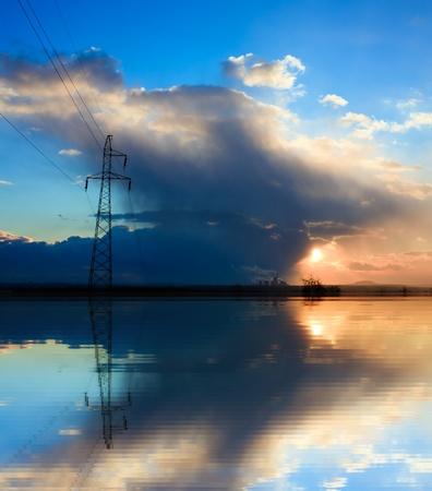 over voltage: Blue power, high voltage electricity pylon over sunset