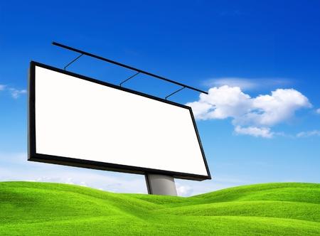 Blank billboard on green meadow photo