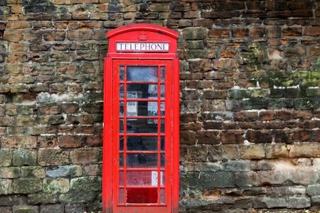 The British red phone booth on old wall photo