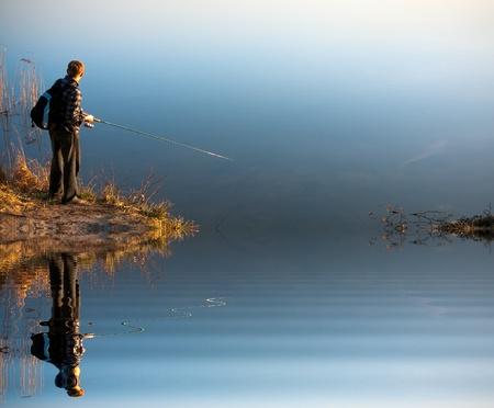 hombre pescando: Pescando en un lago