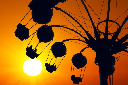 theme parks: Amusement ride on golden sunset Stock Photo