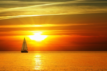 Sailboat on the ocean at sunset photo