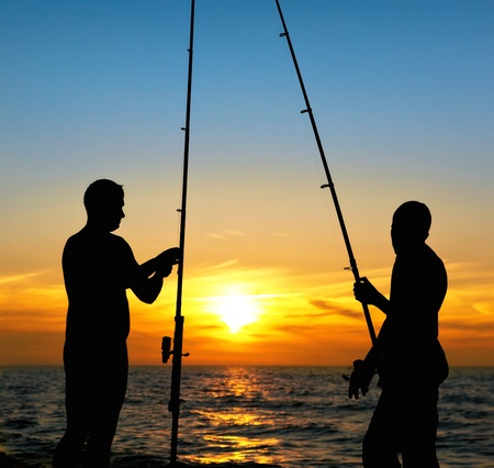 Silhouette of father and son fishing at sunset photo