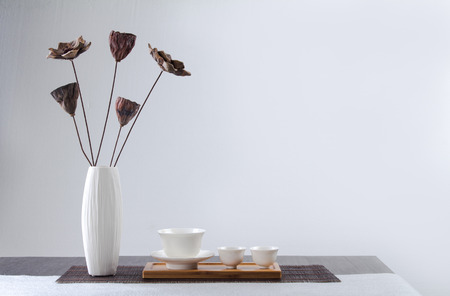 Tea cups with flower vase on table