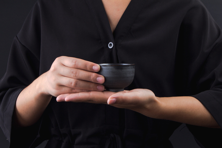 Hand holding a cup of Chinese tea