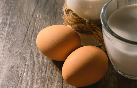A mug of milk and eggs on the table Stock Photo