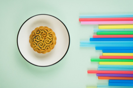 Mooncake served in a plate with colourful straw at the side