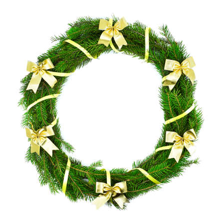 Christmas wreath made of natural fir branches, decorated with gold bows on a white background. Christmas holiday. Foto de archivo