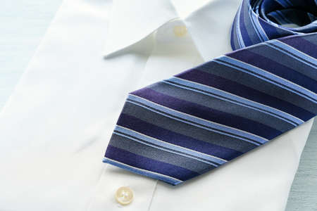 Men's dress shirt and tie on white background