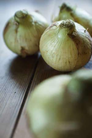 Raw unpeeled onions on wooden table