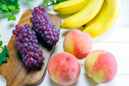 Fresh peaches, grapes and bananas on wooden table