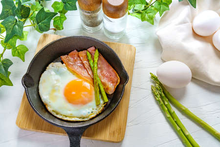 Fried egg, asparagus and bacon on wooden table