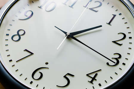Close up of a clock isolated on wooden table