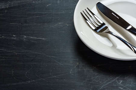 Empty plate, knife and fork on wooden table