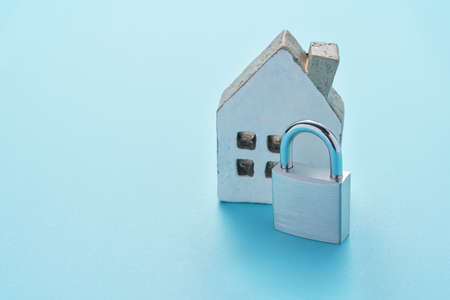 Padlock and miniature house on color background