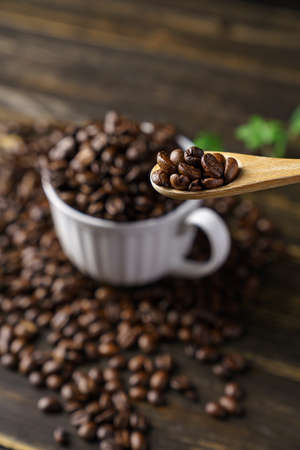 Coffee beans and cup on wooden table 免版税图像