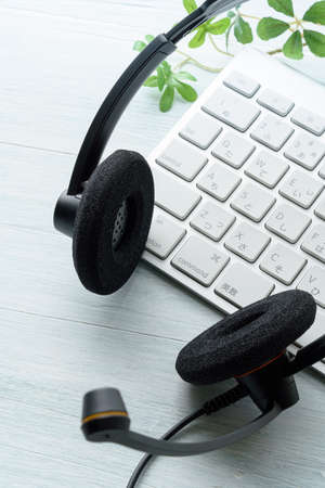 Headset and computer keyboard on wooden table