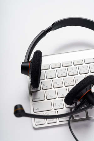 Headset and computer keyboard on white background 免版税图像