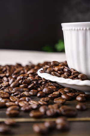 Hot coffee and coffee beans on wooden background