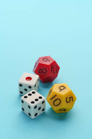 Two white dice and multi sided dice on color background