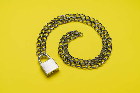 Padlock and chain on color background