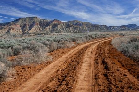 Sandy soil: Carretera del desierto: Un camino de tierra �spero lleva en el desierto del norte de Fruita en el oeste de Colorado. Foto de archivo