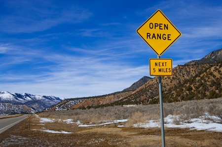 warned: Open Range Sign:  Motorists are warned to watch for cattle along a stretch of road in western Colorado. Stock Photo
