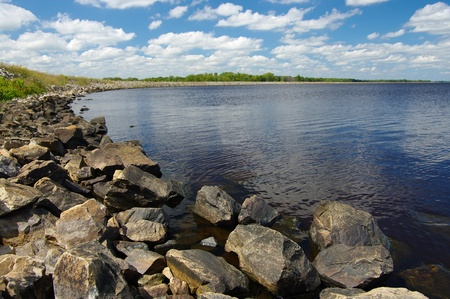 resulted: Rocky Shoreline:  Large boulders help to form a side of Petenwell Lake in central Wisconsin. This lake resulted from the creation of Petenwell Dam,  Stock Photo