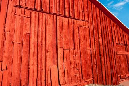 Oude schuur met nieuwe verf: verse rode kleur helderder de kant van een verweerde schuur. Stockfoto